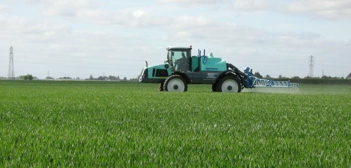 Sprayer In Wheat Field
