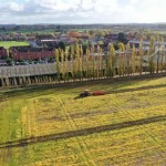 201125-aerial-view-of-tractor-working-in-a-field-with-a-r703173